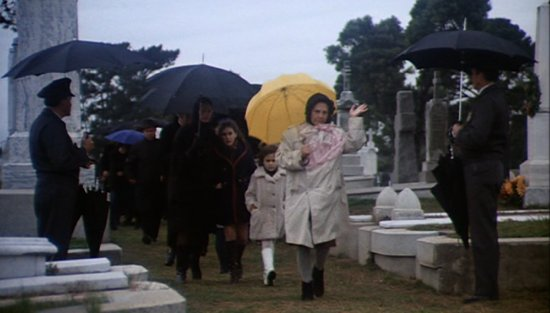 Dame Marjorie Chardin, alias Maude, with a yellow umbrella.