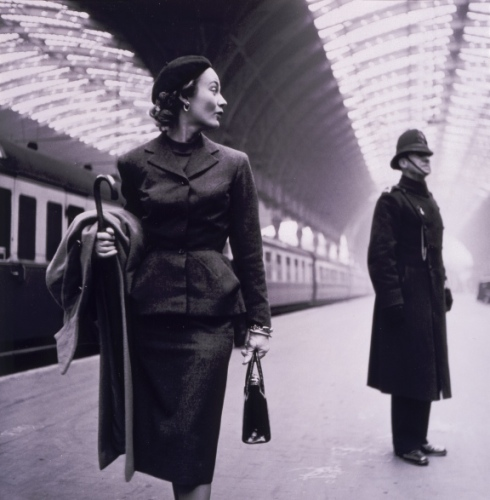 A model at Victoria Station in London. The pencil skirt, wrist-length gloves, and beret were typical signs of fragility in 1950s fashion.
