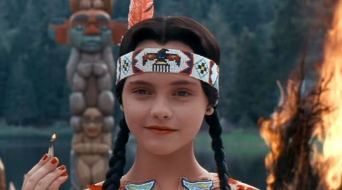 Wednesday Addams. Smiling.