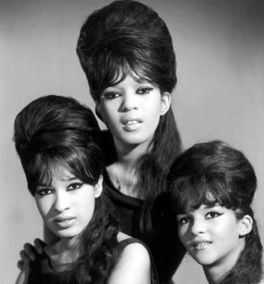 The Ronettes wearing white lipstick with a bouffant hairstyle.